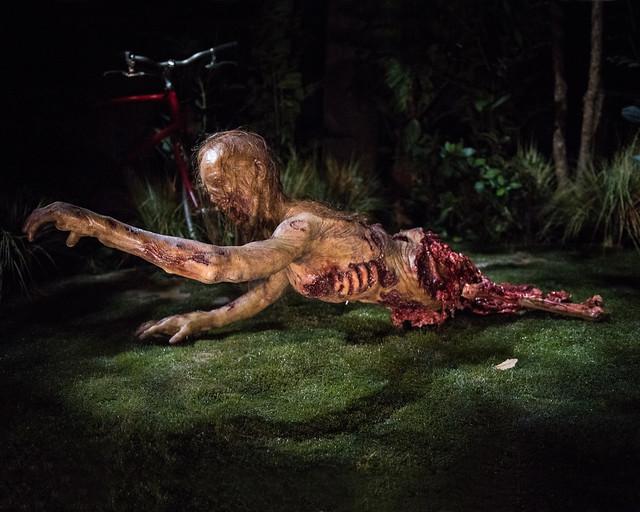 Espeluznante caminante de la atracción de The Walking Dead, sin la mitad del cuerpo, arrastrándose por el suelo