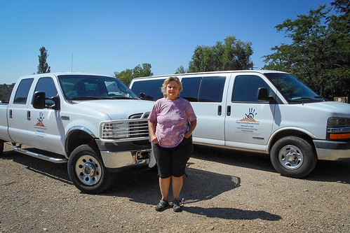 Janet Ross, founder and Executive Director of the Four Corners School of Outdoor Education, in front of a van and truck