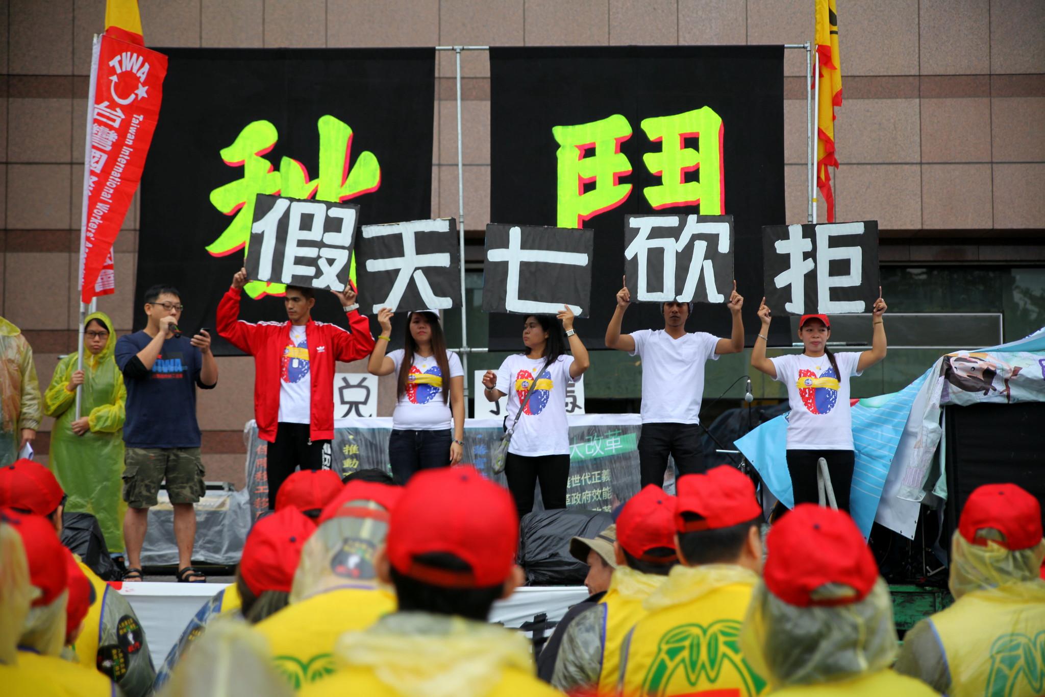 移工高舉「拒砍七天假」,工人的權利無國界。(攝影:陳逸婷)