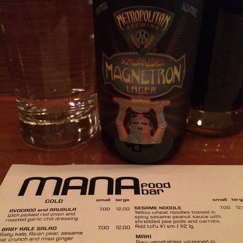 A bottle of Metropolitan Brewing's Magnetron above a MANA menu.