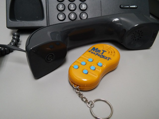 A phone off the hook with a 'Mr. T in your pocket' keychain positioned at the mouthpiece.