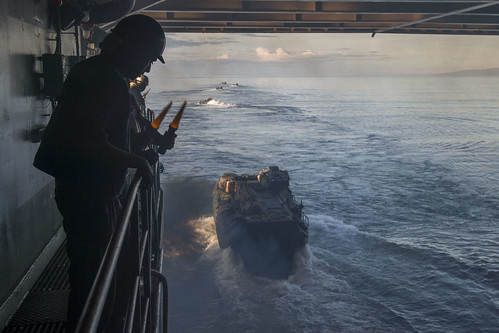 Sailors and Marines launch amphibious assault vehicles (AAV) from the well deck of the dock landing ship USS Rushmore.