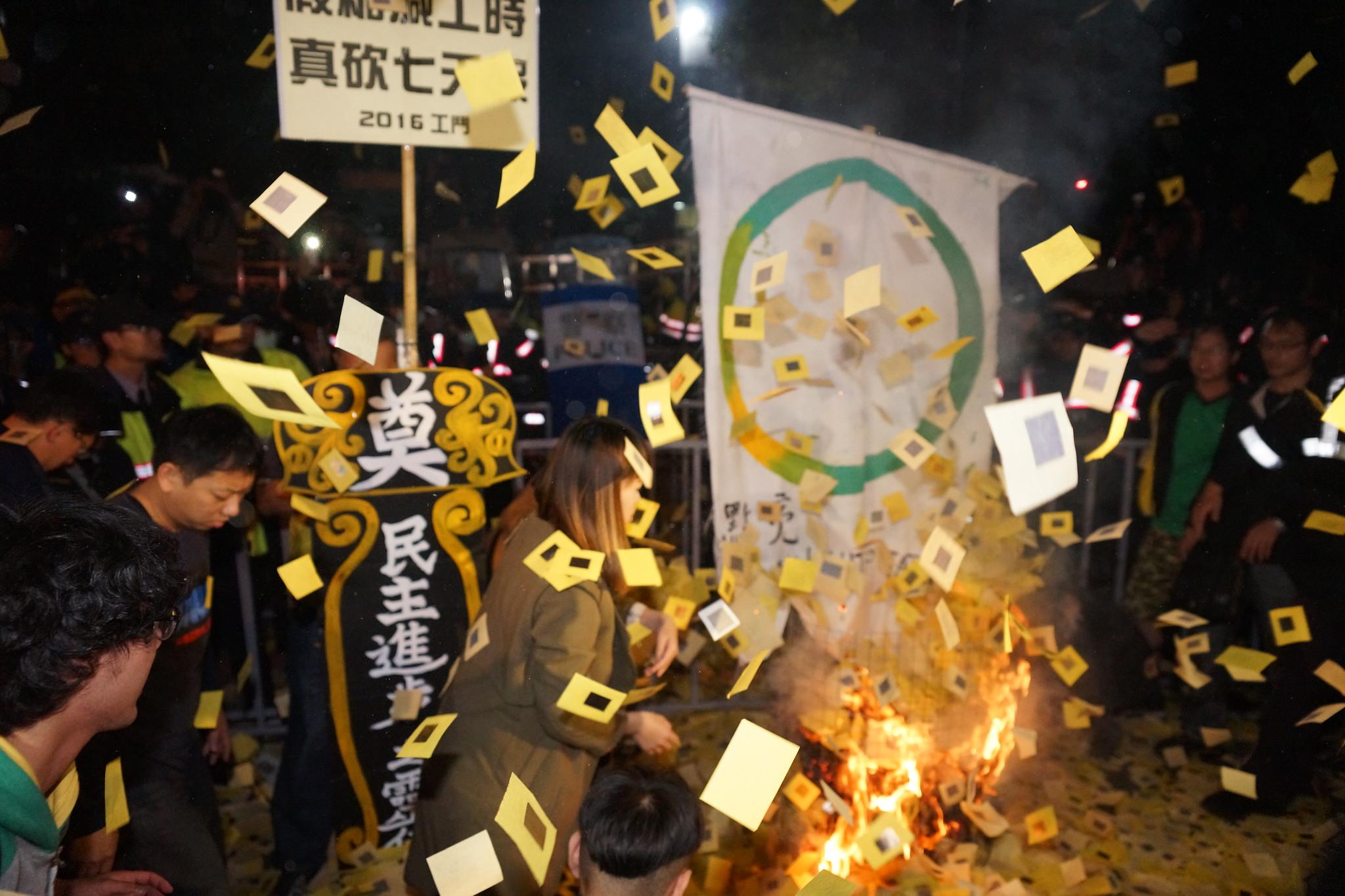 """劳团在立院外焚烧""""点亮彩立方""""旗帜与冥纸。(摄影:王颢中)"""
