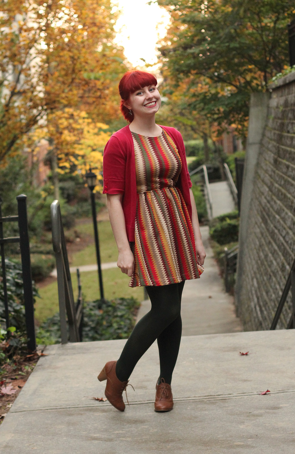 Autumnal Outfit: Red Short Sleeved Cardigan, Chevron Multicolored Modcloth Dress, Dark Green Tights, and Brown Oxford Heels