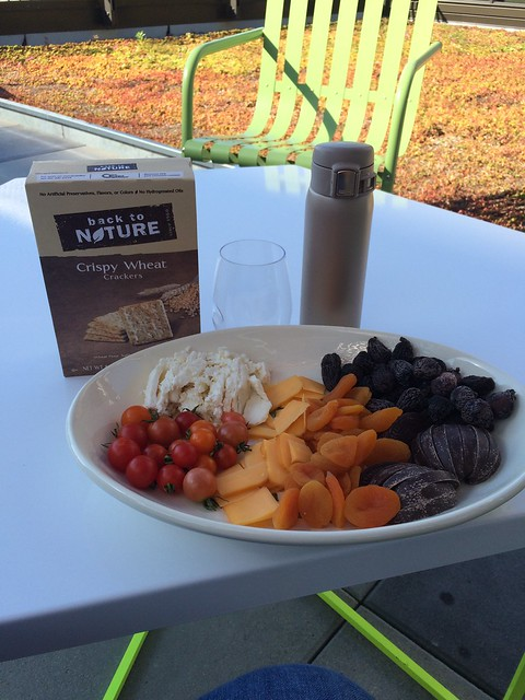 Box of crackers. Platter of fruits, cheese, tomatoes, and chocolate. Most importantly? A wine glass! (Also, the travel mug is water.)