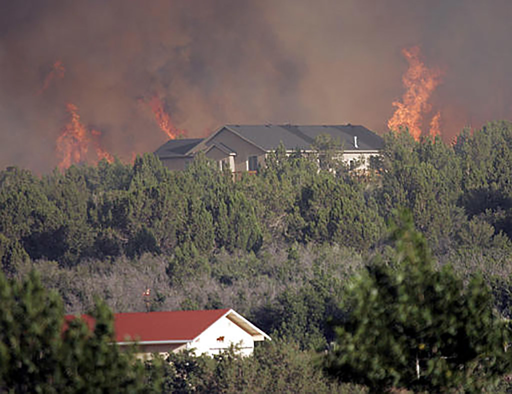 A wildland fire burning in front of houses and trees flickr for Building a defensible home
