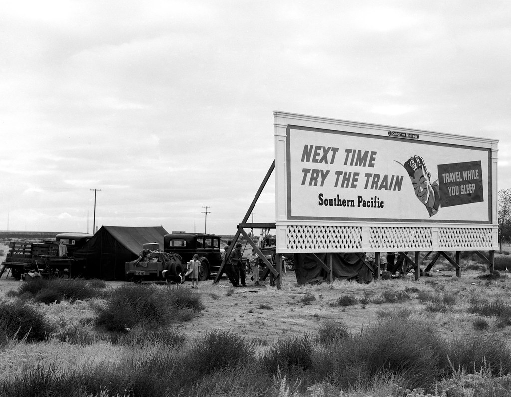 "Camped in the rain behind billboard: three families, fourteen children. On U.S. 99. Near Famosa, Kern County, California. Nov, 1939. Sign for Southern Pacific says, ""Next Time Try The Train."""