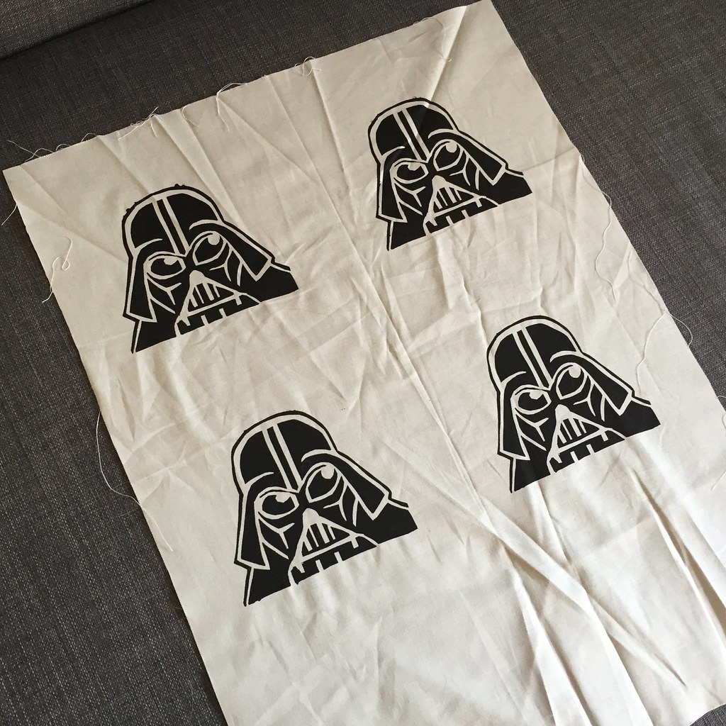 four Darth vader motifs screen printed in black onto a light grey fabric