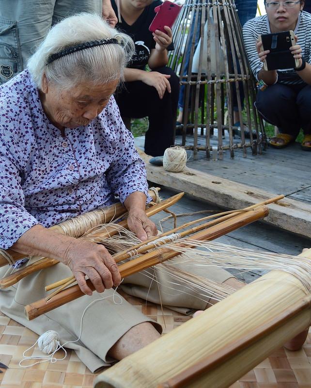 高齡96歲的朱阿菊是國寶級的香蕉絲編織師傅,正在專注使用地織機織作。(攝影:謝宗璋)
