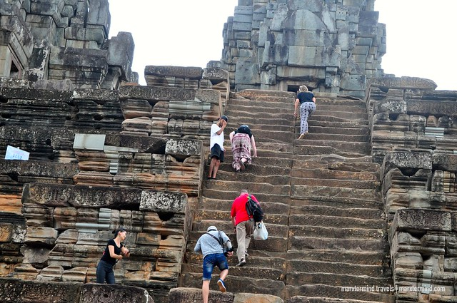 Tourists Climbing the Steep Stairs of Ta Keo