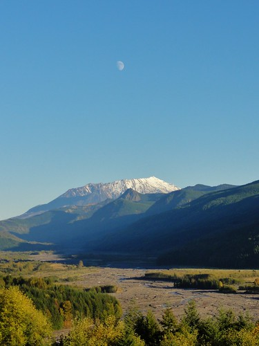 Image shows Mount St. Helens from Hoffstadt Bluffs, with the Toutle River valley in the foreground. The sky is a clear blue. The moon is visible above the volcano.