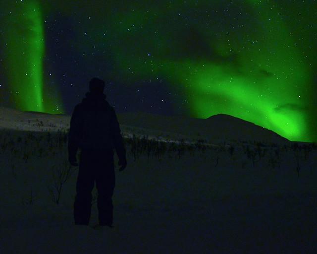 Caminando por la nieve en la noche mientras vemos la Aurora Boreal