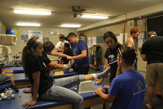 Athletic Trainers taping athlete's ankles