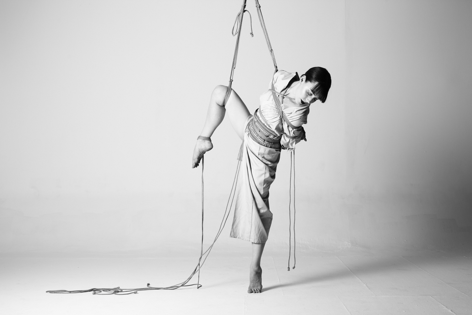 dark haired woman wearing a kimono tied in a shibari partial suspension