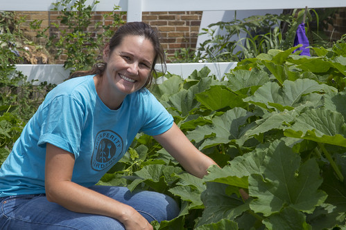 Nicole Bridges, garden programmer, sitting next to one of the many garden beds