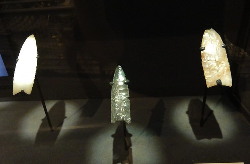 Image shows three Clovis spear points on display in a black case. One is white, one is dark gray, and the final one is tan.
