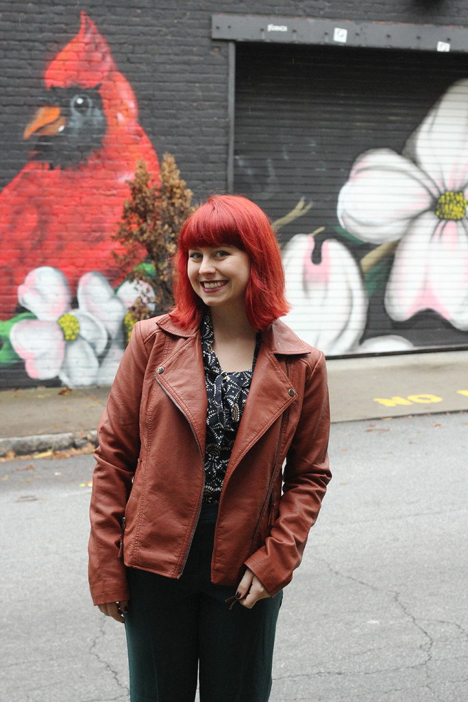 Warm Brown Faux Leather Jacket, Patterned Navy Top, and Bright Red Hair