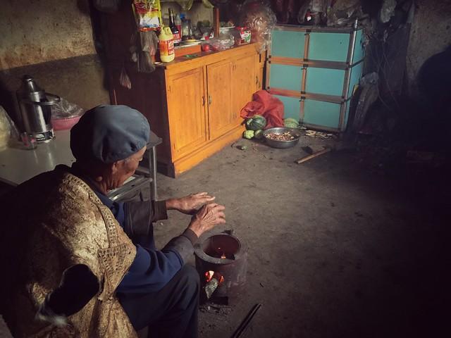 Anciano calentando sus manos en el fuego (Tierras Rojas de Dongchuan, Yunnan)