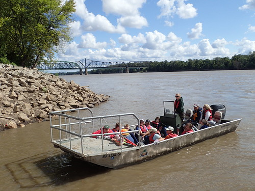 An MDC boat driver takes a group of volunteers out on the river