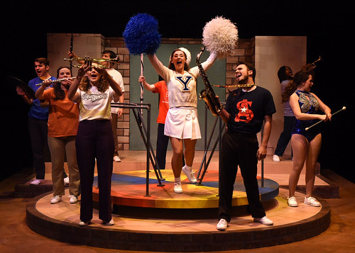 "The cast of ""Is There Life After High School?"" mimics the actions of band members at a football game on stage."