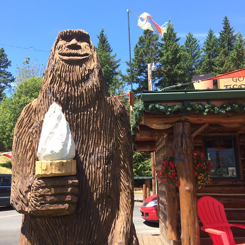 A large scuplture, clearly made with a chainsaw, of Bigfoot holding an ice cream cone.
