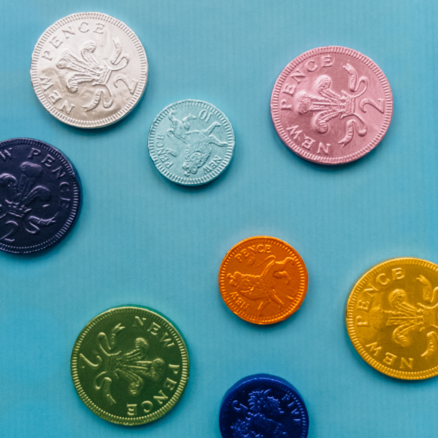 colourful chocolate coins on blue background