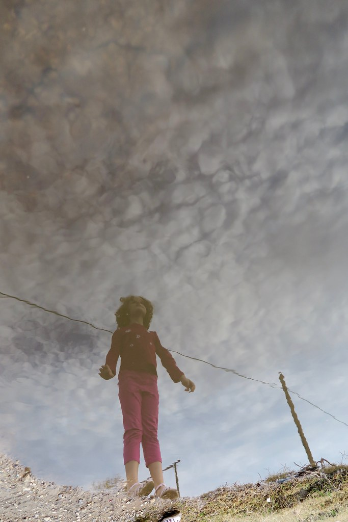puddle reflection of Anais on a cloudy sky