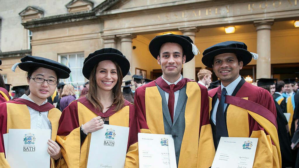 Graduates in gowns show their certificates in front of Bath Assembly Rooms