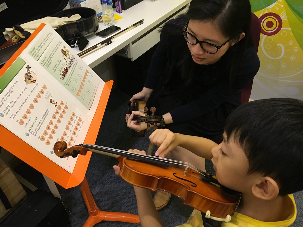 Asher plucking the strings during his first lesson.