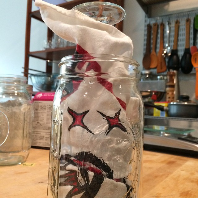 An upside-down champagne flute wrapped in a kitchen towel, stuffed into a quart mason jar.