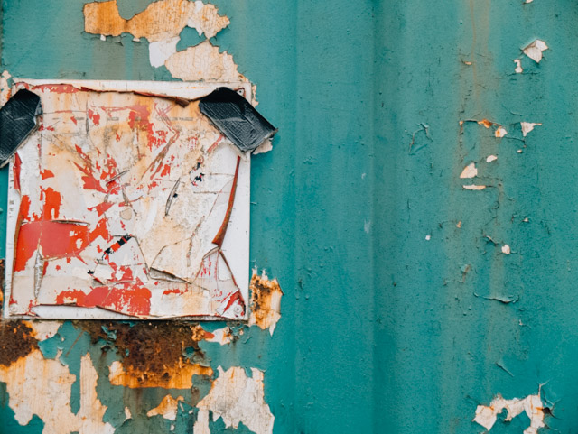 worn down sign on rusty turquoise shed