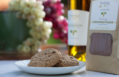 WholeVine gluten-free Chardonnay grape seed flour bag beside a plate of cookies and a bottle of wine with red and white grapes behind them