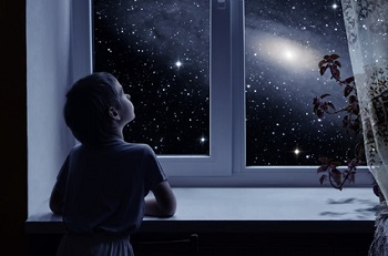 Boy looking out at starry sky