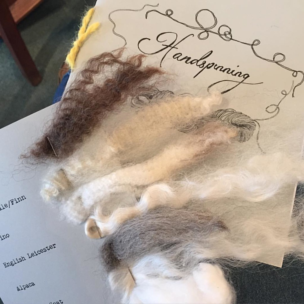a card with different types of fleece attached, with an information booklet on spinning in the background