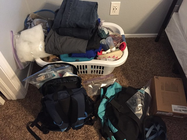 Two backpacks full of travel gear in front of a laundry basket also full of travel gear.
