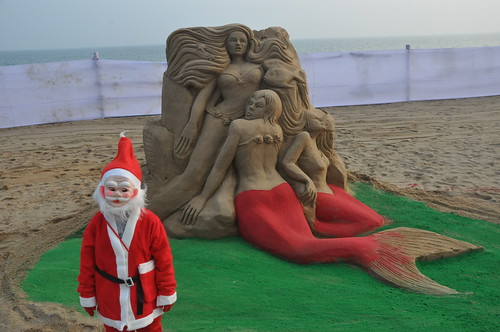 On the eve of Christmas Sand artist Manas Kumar Sahoo creates sand sculpture on the Golden Sea-Beach