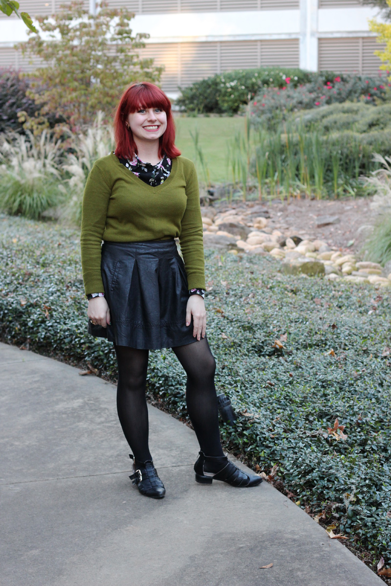 Floral Print Top Under an Olive Green Sweater, Faux Leather Pleated Skirt, Black Tights, and Pointed Cutout Flats