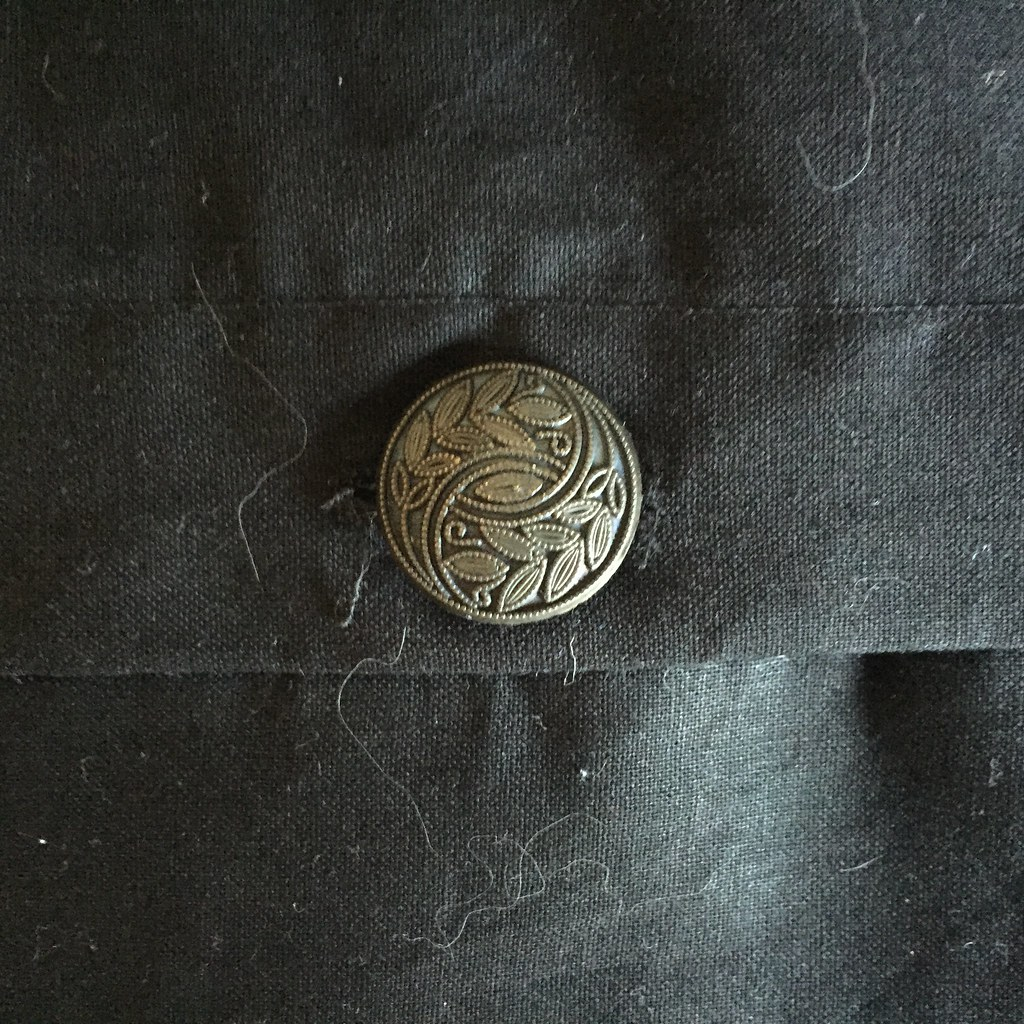 brass computed ornate button on black fabric