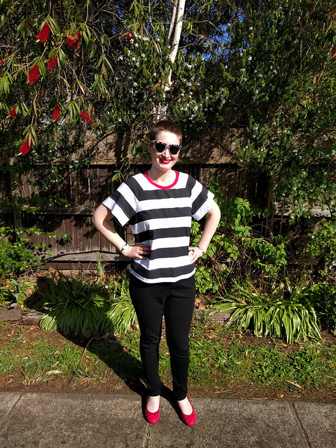 A woman poses in a garden, wearing a black and white striped tee and black ponte pants.