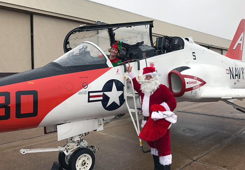 Santa Claus and an elf get out of a T-45C Goshawk for a Christmas party.