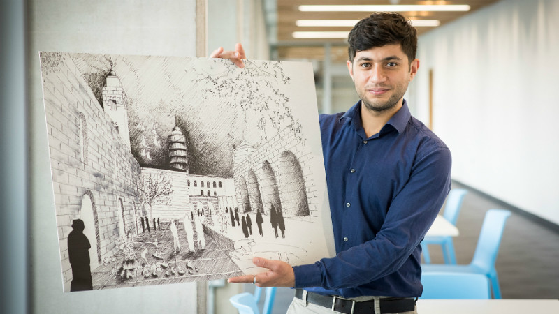 Ammar Azzouz holds one of his hand drawings.