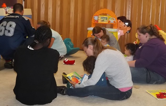 Parents reading to their children at Baby U