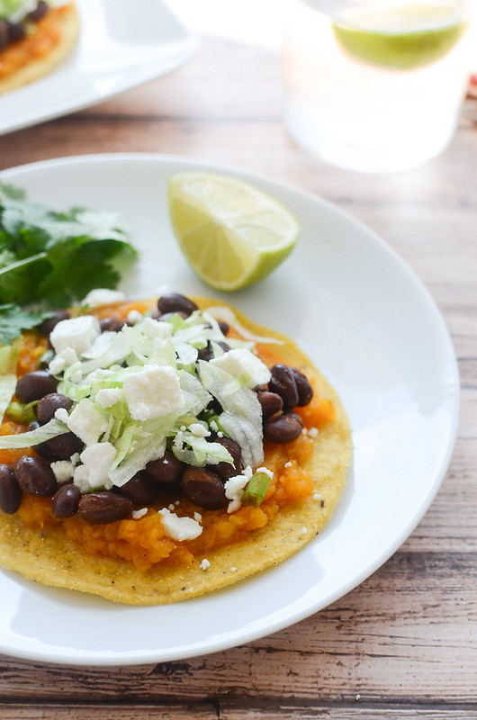 Butternut Squash and Black Bean Tostadas - black beans seasoned with chili powder and lime juice on top of butternut squash and crunchy tostadas. Topped with queso fresco and crisp lettuce. Perfect for meatless Monday!