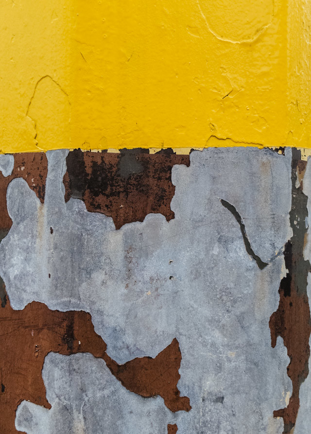 yellow paint on rusted lamppost