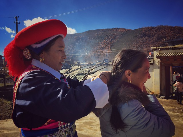 Mujer tibetana peinando a la hermana de la novia en una boda en Shangri-La (Yunnan, China)
