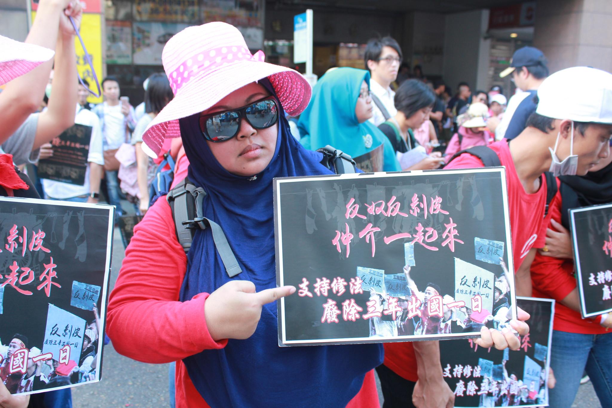 參與遊行的移工舉起訴求,在仲介公會的門前,要求仲介不應再繼續剝移工的皮,一起推動《就服法》修法。(攝影:張宗坤)