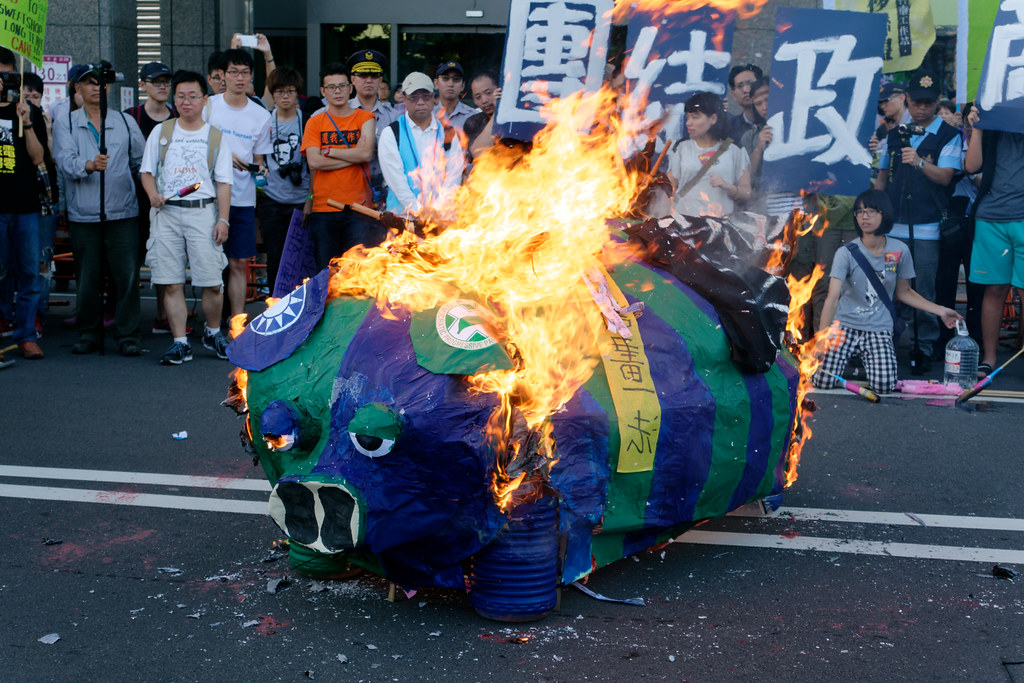 """图为2015年""""秋斗"""",社运团体焚毁纸扎的蓝绿小猪,宣示向两大党斗争的决心。(资料照/摄影:林佳禾)"""