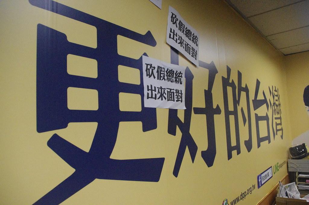 學生將標語貼在民進黨部辦公室。(攝影:高若想)
