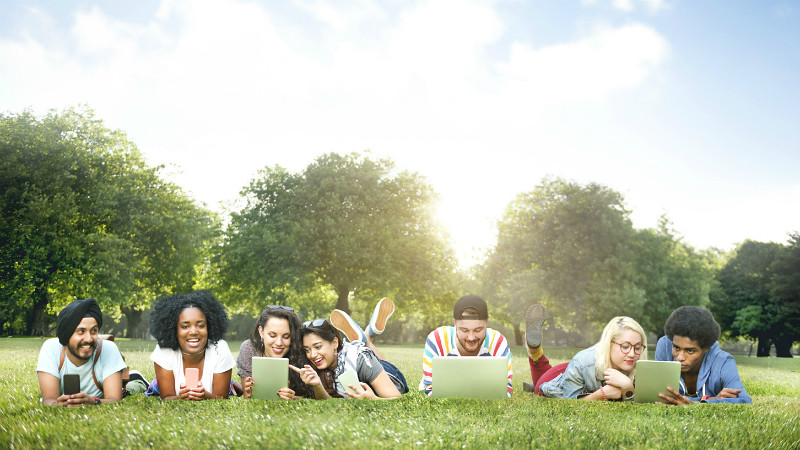 Young people lying on grass looking at laptops and tablets
