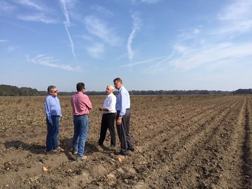 Under Secretary Michael Scuse, North Carolina FSA State Executive Director Bob Etheridge, and FSA County Executive Director Kenny Johnson standing with farmer Kent Smith